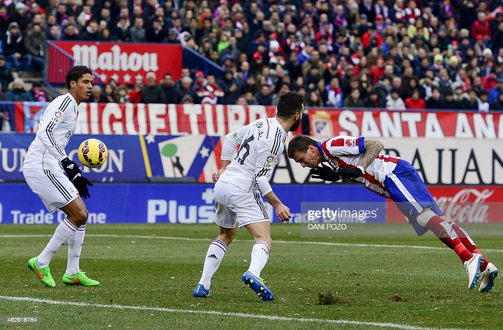 Atletico Madrid's Croatian forward <a gi-track='captionPersonalityLinkClicked' href=/galleries/search?phrase=Mario+Mandzukic&family=editorial&specificpeople=4476149 ng-click='$event.stopPropagation()'>Mario Mandzukic</a> (R) heads to score past Real Madrid's defender <a gi-track='captionPersonalityLinkClicked' href=/galleries/search?phrase=Dani+Carvajal+-+Spanish+Soccer+Defender&family=editorial&specificpeople=7916431 ng-click='$event.stopPropagation()'>Dani Carvajal</a> (C) during the Spanish league football match Club Atletico de Madrid vs Real Madrid CF at the Vicente Calderon stadium in Madrid on February 7, 2015. Atletico won 4-0.