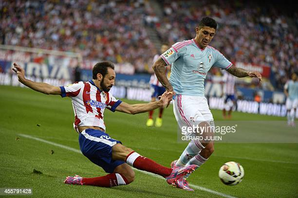 Atletico Madrid's defender Juanfran vies with Celta Vigo's Chilean midfielder Pablo Hernandez during the Spanish league football match Club Atletico...