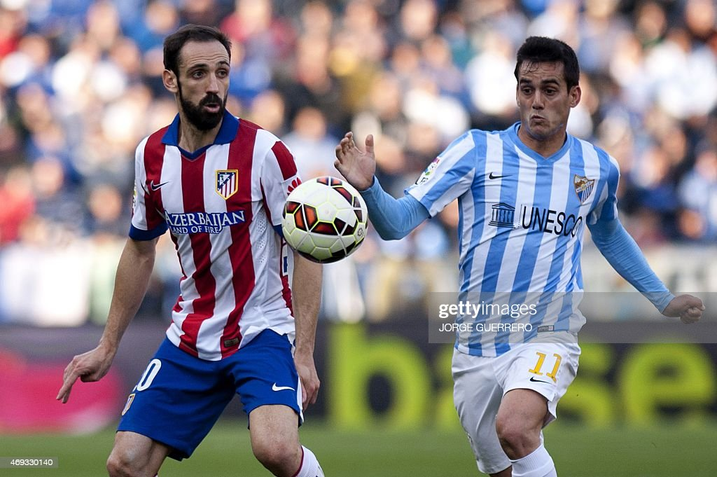 Atletico Madrid's defender Juanfran vies with Malaga's forward Juanmi during the Spanish league football match Malaga CF vs Club Atletico de Madrid...