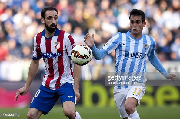 Atletico Madrid's defender Juanfran vies with Malaga's forward Juanmi during the Spanish league football match Malaga CF vs Club Atletico de Madrid...