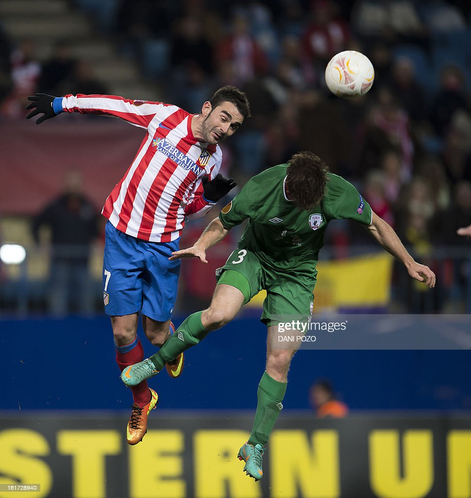 Atletico Madrid's forward Adrian Lopez (L) heads the ball during the UEFA Europa league round of 32 first leg football match Atletico de Madrid vs FC Rubin Kazan at the Vicente Calderon stadium in Madrid on February 14, 2013.