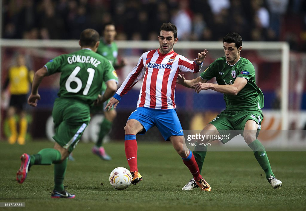Atletico Madrid's forward Adrian Lopez (C) vies with Rubin Kazan's Spanish defender Ivan Marcano (R) during the UEFA Europa league round of 32 first leg football match Atletico de Madrid vs FC Rubin Kazan at the Vicente Calderon stadium in Madrid on February 14, 2013. AFP PHOTO / DANI POZO