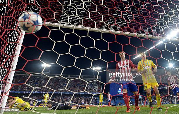 Atletico Madrid's forward Fernando Torres and Astana's Slovenian defender Branko look at the ball inside the goal net after Atletico de Madrid scored...