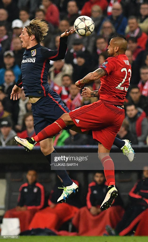 Atletico Madrid's forward Fernando Torres (l) AND Bayern Munich's Chilean midfielder Arturo Vidal vie for the ball during the UEFA Champions League semi-final, second-leg football match between FC Bayern Munich and Atletico Madrid in Munich, southern Germany, on May 3, 2016. / AFP / LUKAS