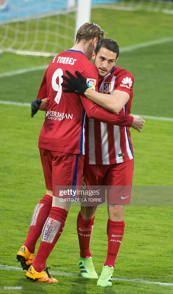Atletico Madrid's forward Fernando Torres (L) celebrates a goal with Atletico Madrid's midfielder Koke during the Spanish league football match Getafe CF vs Club Atletico de Madrid at the Coliseum Alfonso Perez stadium in Getafe on February 14, 2016. / AFP / CURTO DE LA TORRE