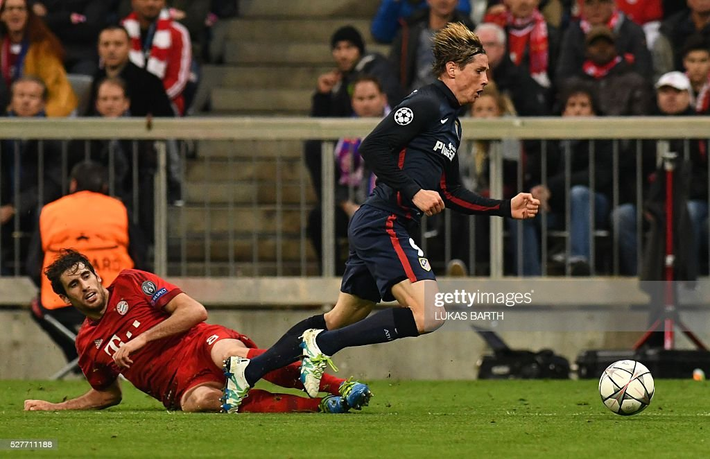Atletico Madrid's forward Fernando Torres is fouled by Bayern Munich's Spanish midfielder Javier Martinez for a penalty during the UEFA Champions League semi-final, second-leg football match between FC Bayern Munich and Atletico Madrid in Munich, southern Germany, on May 3, 2016. / AFP / LUKAS