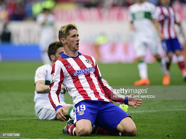 Atletico Madrid's forward Fernando Torres slides on his knees during the Spanish league football match Club Atletico Madrid vs Elche FC at the...