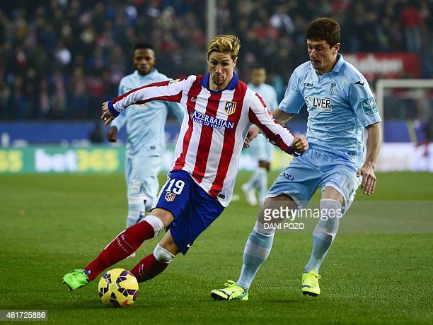 Atletico Madrid's forward Fernando Torres vies with Granada's midfielder Francisco Medina 'Piti' during the Spanish League football match Club...