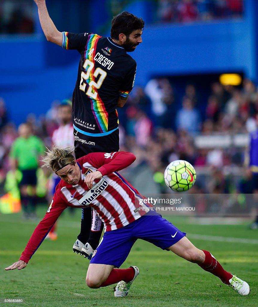 Atletico Madrid's forward Fernando Torres (bottom) vies with Rayo Vallecano's midfielder Crespo during the Spanish league football match Club Atletico de Madrid vs CF Rayo Vallecano at the Vicente Calderon stadium in Madrid on April 30, 2016. / AFP / PIERRE