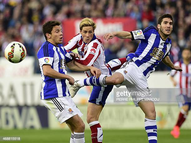 Atletico Madrid's forward Fernando Torres vies with Real Sociedad's defender Ruben Pardo and Real Sociedad's defender Joseba Zaldua during the...