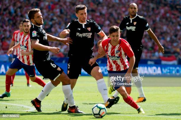 Atletico Madrid's forward from Argentina Luciano Vietto vies with Sevilla's defender from France Clement Lenglet and Sevilla's midfielder from...