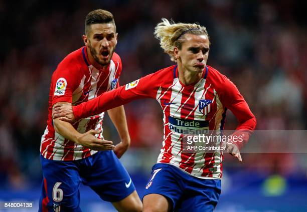 Atletico Madrid's forward from France Antoine Griezmann celebrates with Atletico Madrid's midfielder from Spain Koke after scoring during the Spanish...