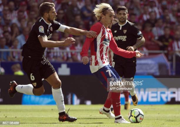 Atletico Madrid's forward from France Antoine Griezmann vies with Sevilla's midfielder from Portugal Daniel Carrico during the Spanish league...