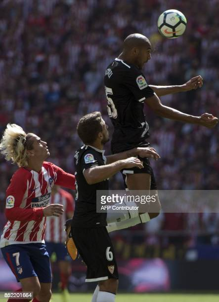 Atletico Madrid's forward from France Antoine Griezmann vies with Sevilla's midfielder from Portugal Daniel Carrico and Sevilla's defender from...