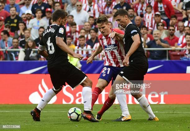 Atletico Madrid's forward from France Kevin Gameiro vies with Sevilla's defender from France Clement Lenglet and Sevilla's midfielder from Portugal...
