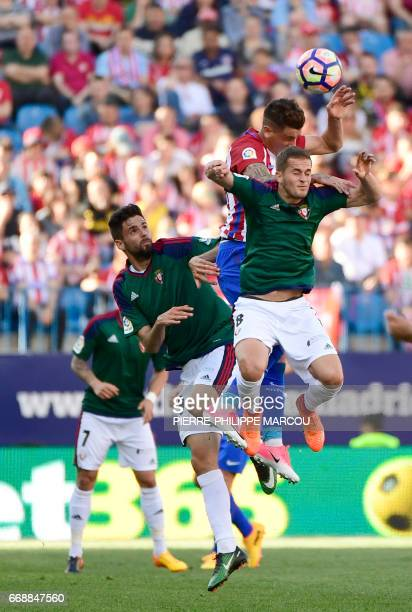 Atletico Madrid's French defender Lucas Hernadez vies with Osasuna's forward Kenan Kodro and Osasuna's midfielder Serbian Goran Causic during the...