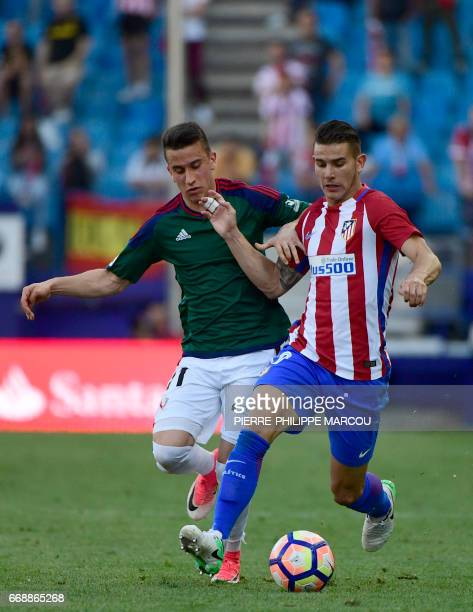 Atletico Madrid's French defender Lucas Hernadez vies with Osasuna's midfielder Alex Berenguer during the Spanish league football match Atletico de...