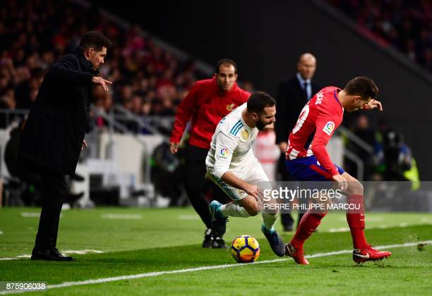 Atletico Madrid's French defender Lucas Hernandez vies with Real Madrid's Spanish defender Dani Carvajal beside Atletico Madrid's Argentinian coach...