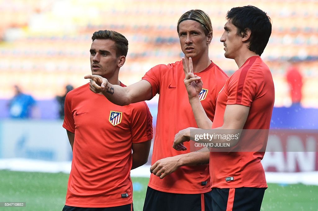 Atletico Madrid's French forward Antoine Griezmann (L), Atletico Madrid's Spanish forward Fernando Torres (C) and Atletico Madrid's Montenegrin defender Stefan Savic speaks during a training session at the San Siro Stadium in Milan, on May 27, 2016, on the eve of the UEFA Champions League final foobtall match between Real Madrid and Atletico Madrid. / AFP / GERARD