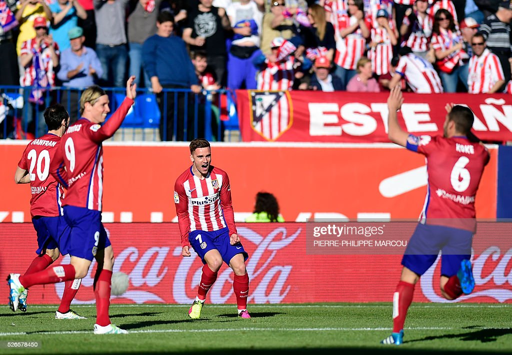 Atletico Madrid's French forward Antoine Griezmann (C) celebrates a goal during the Spanish league football match Club Atletico de Madrid vs CF Rayo Vallecano at the Vicente Calderon stadium in Madrid on April 30, 2016. / AFP / PIERRE
