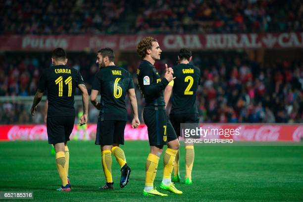 Atletico Madrid's French forward Antoine Griezmann celebrates past teammates after scoring during the Spanish league football match Granada CF vs...