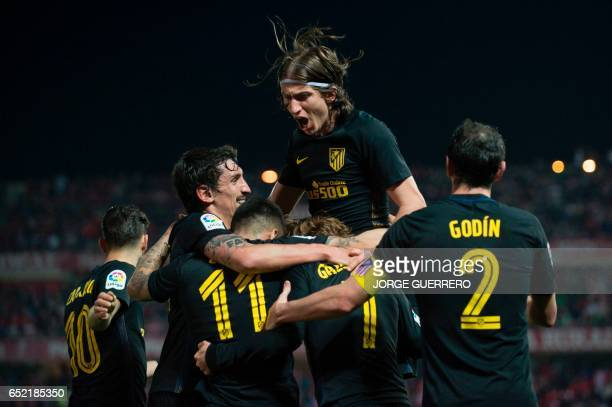Atletico Madrid's French forward Antoine Griezmann celebrates with teammates after scoring during the Spanish league football match Granada CF vs...