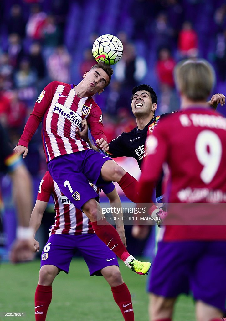Atletico Madrid's French forward Antoine Griezmann (L) heads the ball during the Spanish league football match Club Atletico de Madrid vs CF Rayo Vallecano at the Vicente Calderon stadium in Madrid on April 30, 2016. / AFP / PIERRE