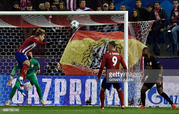 Atletico Madrid's French forward Antoine Griezmann heads the ball to score a goal in front of Galatasaray's Uruguayan goalkeeper Fernando Muslera and...