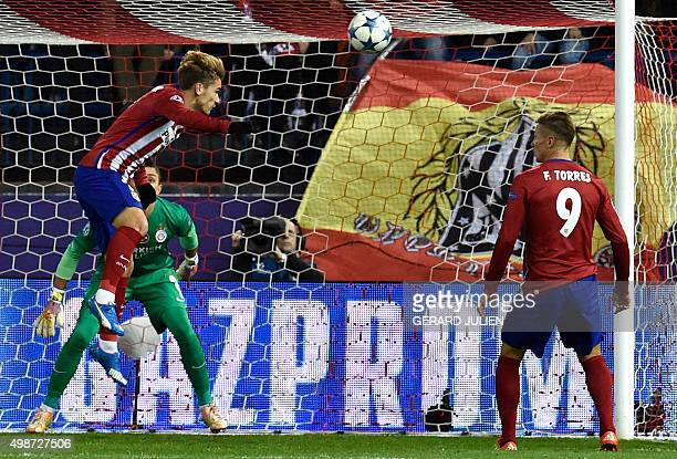 Atletico Madrid's French forward Antoine Griezmann heads the ball to score a goal in front of Galatasaray's Uruguayan goalkeeper Fernando Muslera as...