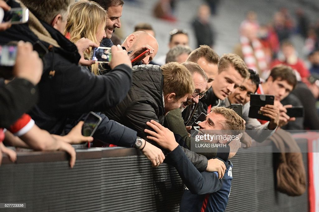 Atletico Madrid's French forward Antoine Griezmann is congratulated after the UEFA Champions League semi-final, second-leg football match between FC Bayern Munich and Atletico Madrid in Munich, southern Germany, on May 3, 2016. / AFP / LUKAS