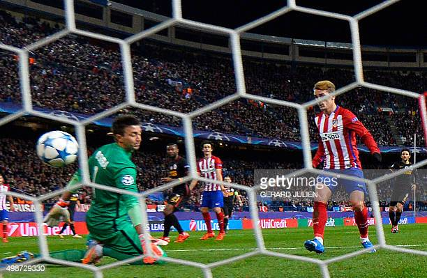 Atletico Madrid's French forward Antoine Griezmann scores a goal as Galatasaray's Uruguayan goalkeeper Fernando Muslera kneels on the pitch during...