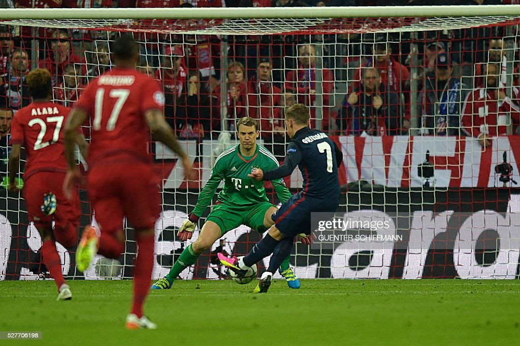 Atletico Madrid's French forward Antoine Griezmann (R) shoots to score past Bayern Munich's goalkeeper Manuel Neuer during the UEFA Champions League semi-final, second-leg football match between FC Bayern Munich and Atletico Madrid in Munich, southern Germany, on May 3, 2016. / AFP / GUENTER