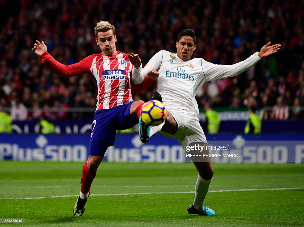 TOPSHOT - Atletico Madrid's French forward Antoine Griezmann (L) vies with Real Madrid's French defender Raphael Varane during the Spanish league football match Atletico Madrid vs Real Madrid at the Wanda Metropolitan stadium in Madrid on November 18, 2017. /