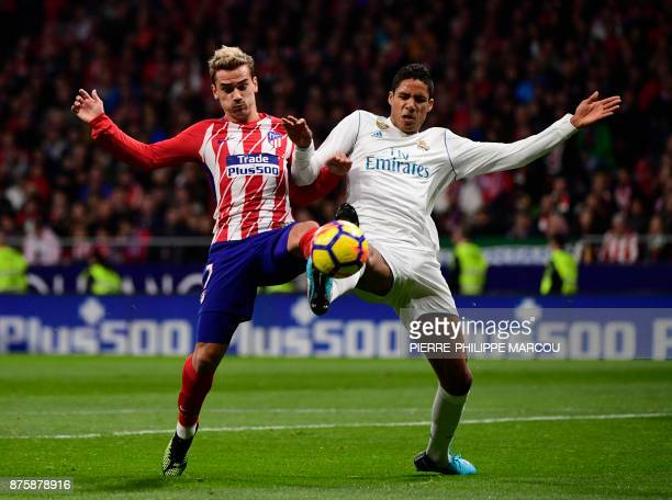 TOPSHOT Atletico Madrid's French forward Antoine Griezmann vies with Real Madrid's French defender Raphael Varane during the Spanish league football...