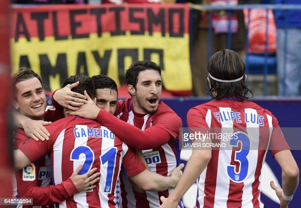 Atletico Madrid's French forward Kevin Gameiro celebrates a goal with teammates during the Spanish league football match Club Atletico de Madrid vs...