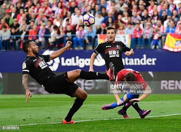 Atletico Madrid's French forward Kevin Gameiro vies with Granada's defender David Lomban during the Spanish league football match Club Atletico de...