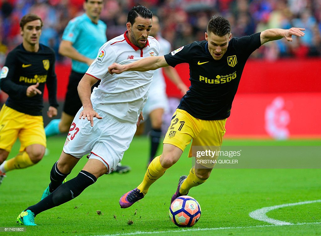 Atletico Madrid's French forward Kevin Gameiro (R) vies with Sevilla's French defender Adil Rami (C) during the Spanish league football match between Sevilla FC and Club Atletico de Madrid at the Ramon Sanchez Pizjuan stadium in Sevilla on October 23, 2016. / AFP / CRISTINA