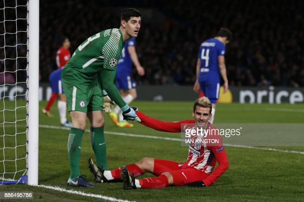 Atletico Madrid's French striker Antoine Griezmann is helped up by Chelsea's Belgian goalkeeper Thibaut Courtois during a UEFA Champions League Group...