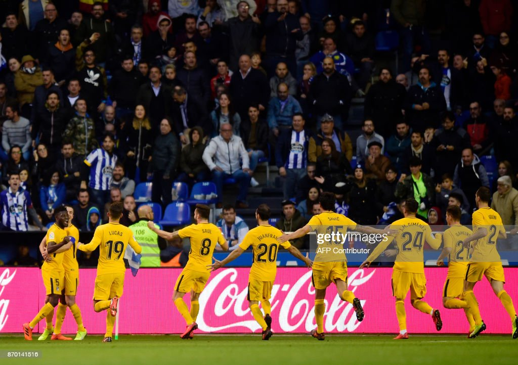 TOPSHOT - Atletico Madrid's Ghanaian midfielder Thomas Partey (L) celebrates with teammates after scoring a goal during the Spanish league football match Deportivo Coruna vs Atletico Madrid at the Riazor stadium in La Coruna on November 4, 2017. /