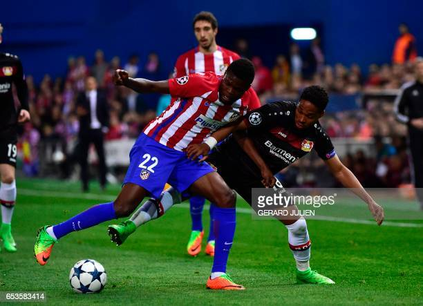 Atletico Madrid's Ghanaian midfielder Thomas Partey vies with Leverkusen's Brazilian defender Wendell during the UEFA Champions League round of 16...