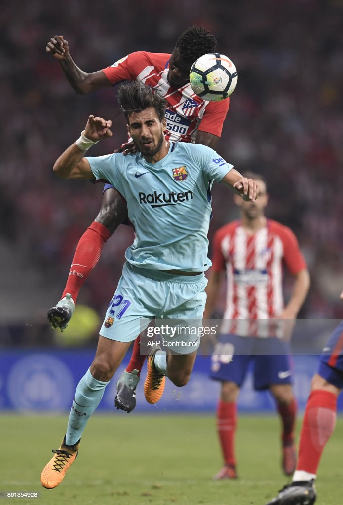 Atletico Madrid's Ghanaian midfielder Thomas (top) vies with Barcelona's Portuguese midfielder Andre Gomes (bottom) during the Spanish league football match Club Atletico de Madrid vs FC Barcelona at the Wanda Metropolitano stadium in Madrid on October 14, 2017. /