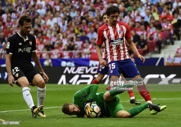 Atletico Madrid's goalkeeper from Slovenia Jan Oblak safes the ball beside Sevilla's midfielder from Italy Franco Vazquez and Atletico Madrid's...