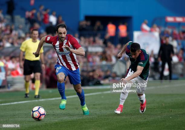 Atletico Madrid's Juanfran is in action against CA Osasuna's Alex Berenguer during the Spanish soccer league La Liga football match Atletico de...