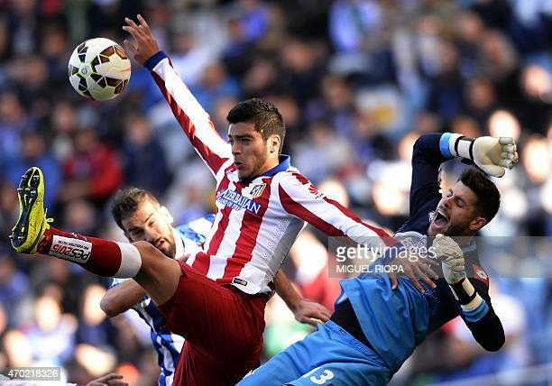 Atletico Madrid's Mexican forward Raul Jimenez jumps for the ball with Deportivo's goalkeeper Fabri and defender Alberto Lopo during the Spanish...