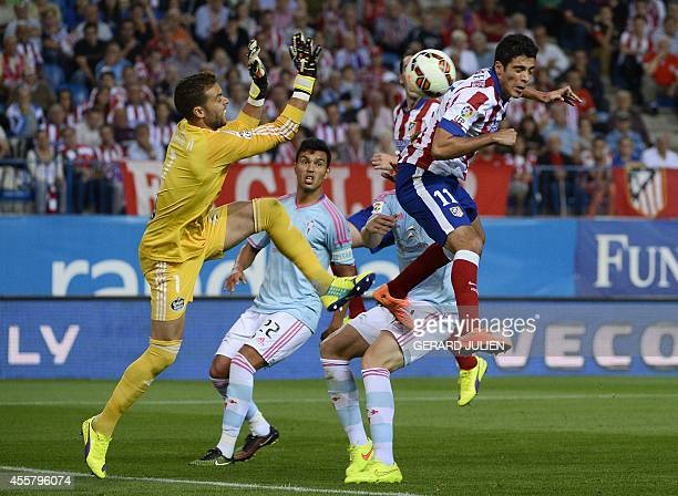 Atletico Madrid's Mexican forward Raul Jimenez vies with Celta Vigo's goalkeeper Sergio Alvarez during the Spanish league football match Club...