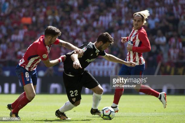 Atletico Madrid's midfielder from Spain Saul Niguez vies with Sevilla's midfielder from Italy Franco Vazquez beside Atletico Madrid's forward from...