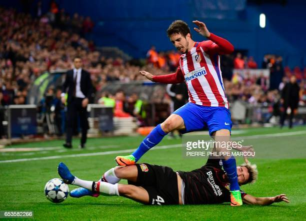 Atletico Madrid's midfielder Gabi is tackled by Leverkusen's Slovanian midfielder Kevin Kampl during the UEFA Champions League round of 16 second leg...