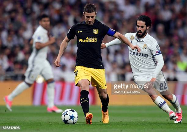 Atletico Madrid's midfielder Gabi vies with Real Madrid's midfielder Isco during the UEFA Champions League semifinal first leg football match Real...