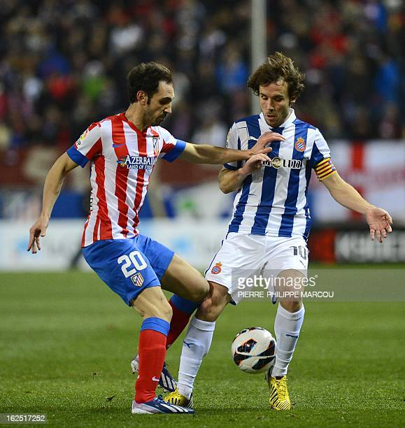Atletico Madrid's midfielder Juanfran vies with Espanyol's midfielder Joan Verdu during their Spanish league football match Atletico de Madrid vs...