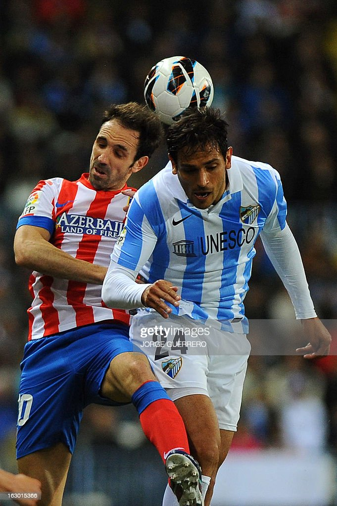 Atletico Madrid's midfielder Juanfran (L) vies with Malaga's Paraguayan forward Roque Santa Cruz during the Spanish league football match Malaga CF vs Atletico de Madrid on March 3, 2013 at Rosaleda stadium in Malaga.